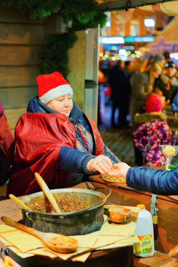 Frauenverkäufer der süßen Mandel nachts Weihnachtsmarkt Riga lizenzfreies stockbild