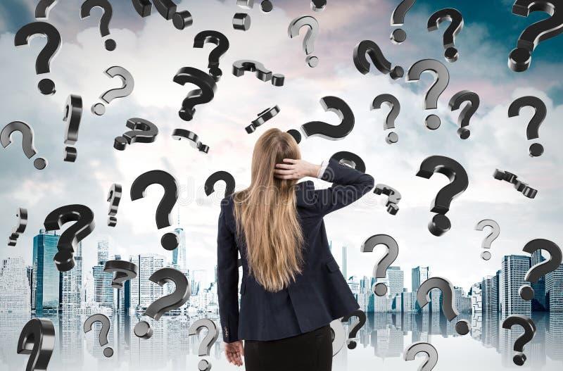 Frauenverkratzen Haupt und Betrachten von den Fragezeichen, die von fallen lizenzfreies stockfoto