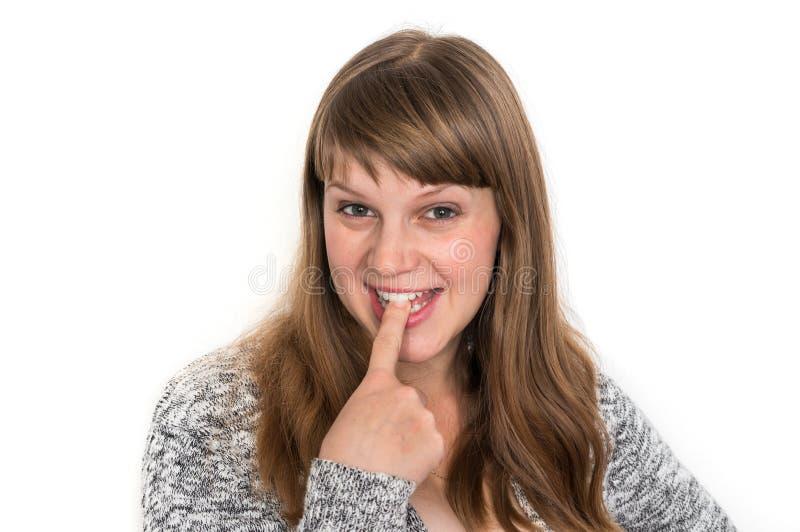 Frauenvertretungszunge und berührt es mit einem Finger lizenzfreies stockbild