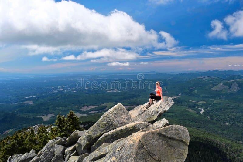 Frauenwanderer auf Felsen über Tal stockfotografie