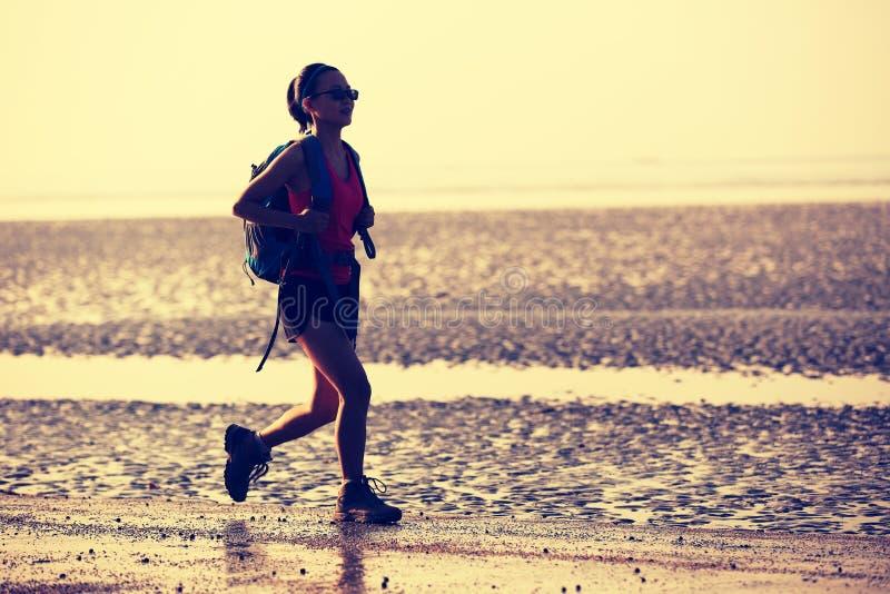 Frauenwanderer, der auf Sonnenaufgangstrand wandert lizenzfreies stockfoto