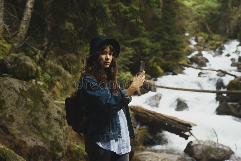 Frauenwanderer, der Foto mit Handy am Wald in Tibet, Porzellan macht lizenzfreies stockfoto