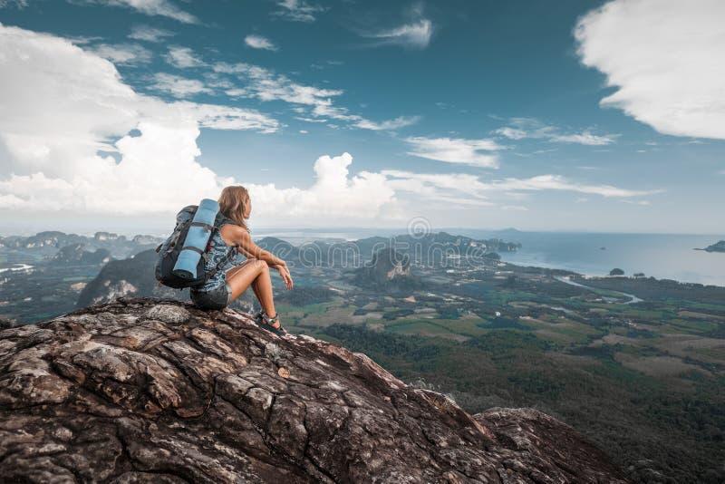 Frauenwanderer sitzt auf einen Berg stockbild