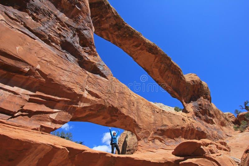 Frauenwanderer wirft an doppeltem O-Bogen an den Bögen Nationalpark, Utah auf stockbilder