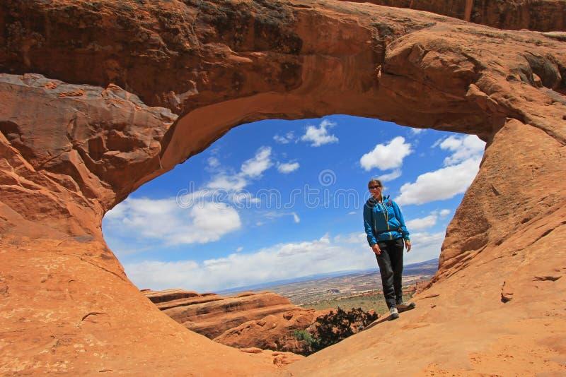 Frauenwanderer wirft am Fach-Bogen an den Bögen Nationalpark, Utah auf stockfotos