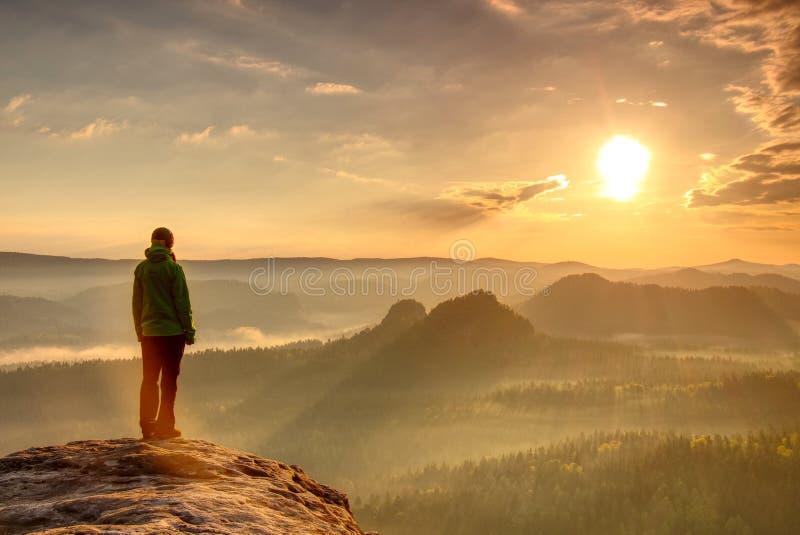 Frauenwandererschattenbild in den Bergen, im Sonnenuntergang und in der Falllandschaft Weiblicher Wanderer, der über Rand schönem stockfotos