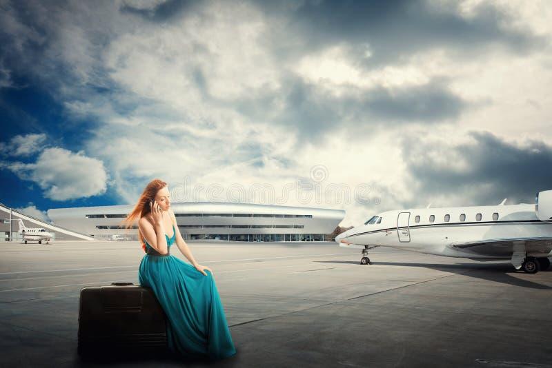 Frauenwarteflugabfahrt, die auf dem Koffer spricht am Telefon sitzt lizenzfreie stockbilder
