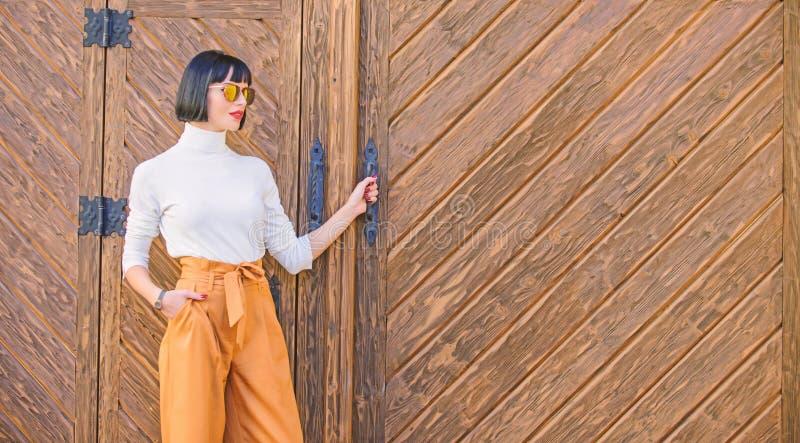 Frauenweg in den losen Hosen Frau moderner Brunette stehen draußen hölzernen Hintergrund Mädchen mit dem Make-up, das herein aufw stockfotografie