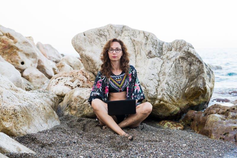 Frauenworkaholicfunktion auf einem Laptop beim Sitzen auf einem Felsen auf dem Strand lizenzfreie stockfotografie