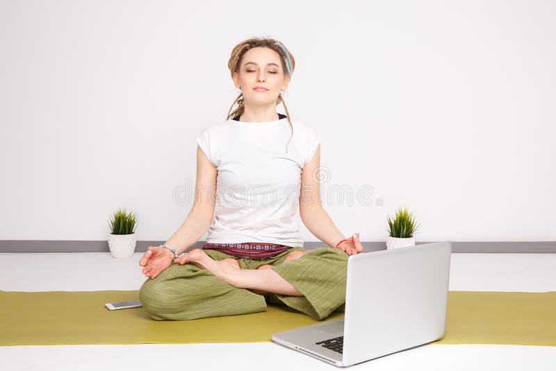 Frauenyoga, das Lotoshaltung auf der grünen Matte auf dem Boden nahe dem Laptop tut lizenzfreie stockfotos