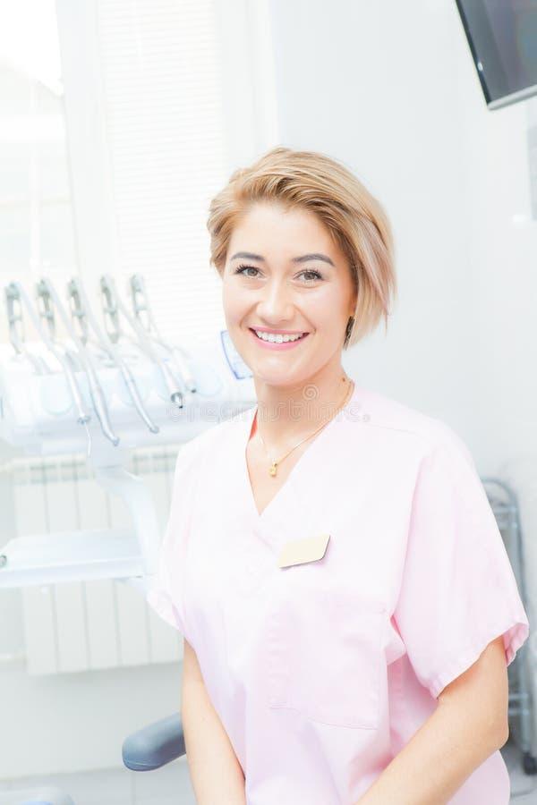 Frauenzahnarztblondine in einem Behandlungsraum stockbild