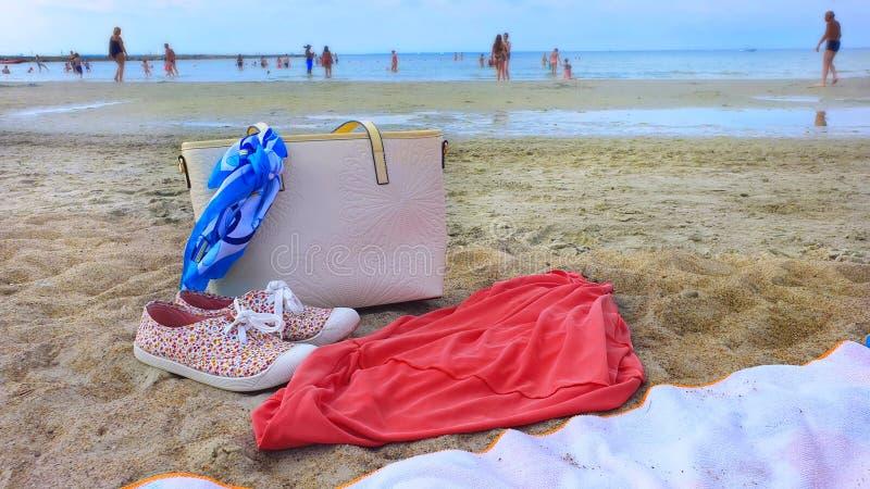 Frauenzusätze Sommerseefeiertag sunglass weiße Handtasche OM der Strandnaturhintergrund Summertim des blauen Himmels des Sandes t lizenzfreies stockfoto