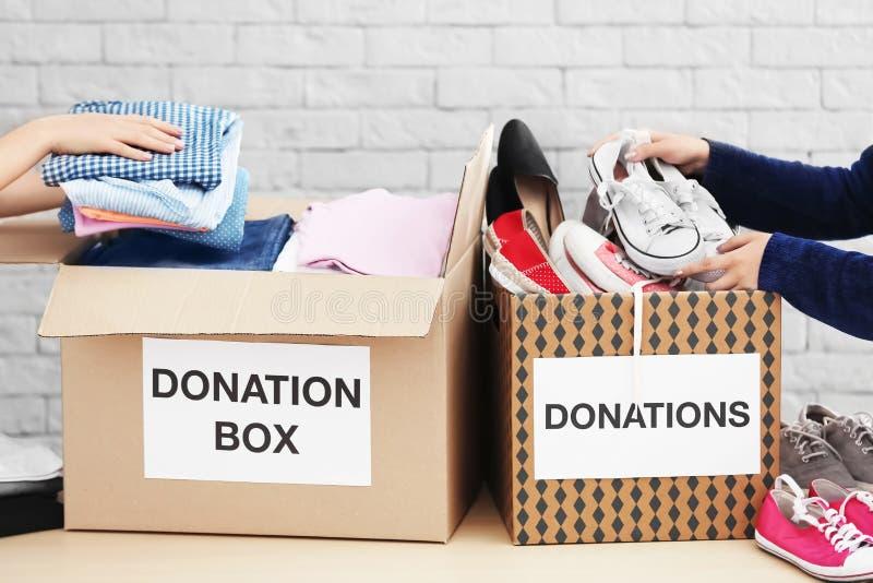 Fraufreiwillige, die Kleidung sammeln stockbild