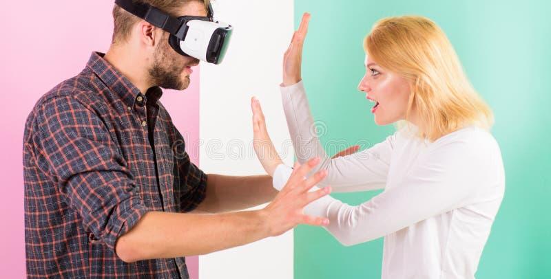 Frauversuche, zum er zurück in wirkliches Leben zu helfen Bemannen Sie mit einbezogenes Videospiel VR Gläser während Mädchenversu stockfotos