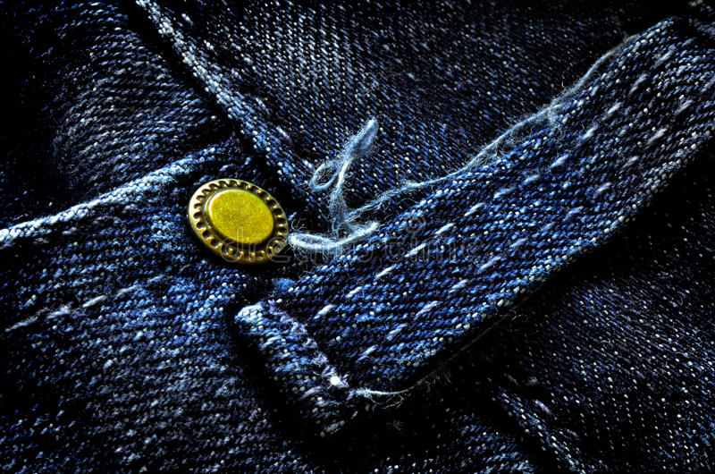 Frayed Denim Pants Button. Frayed denim pants with detail of brass button and seams stock image
