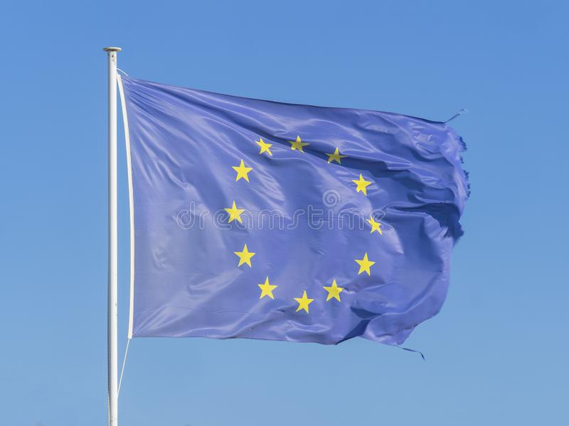 Frayed European Union EU flag is fluttered by wind. Frayed European Union EU flag is fluttered by a strong wind, blue sky background stock photos