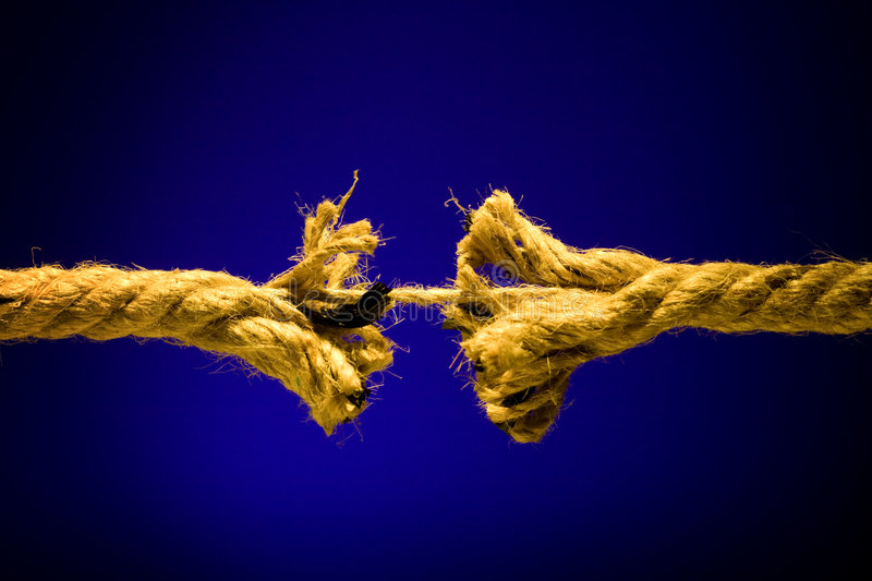 Frayed rope breaking. On a dark background stock images