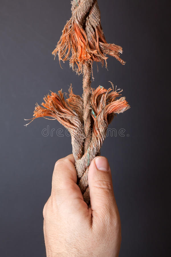 Frayed rope. Breaking rope and hand on dark background stock photos