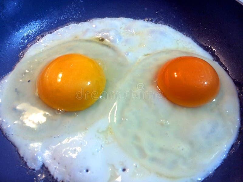 Freír dos diversas yemas de huevo coloreadas de los huevos imágenes de archivo libres de regalías