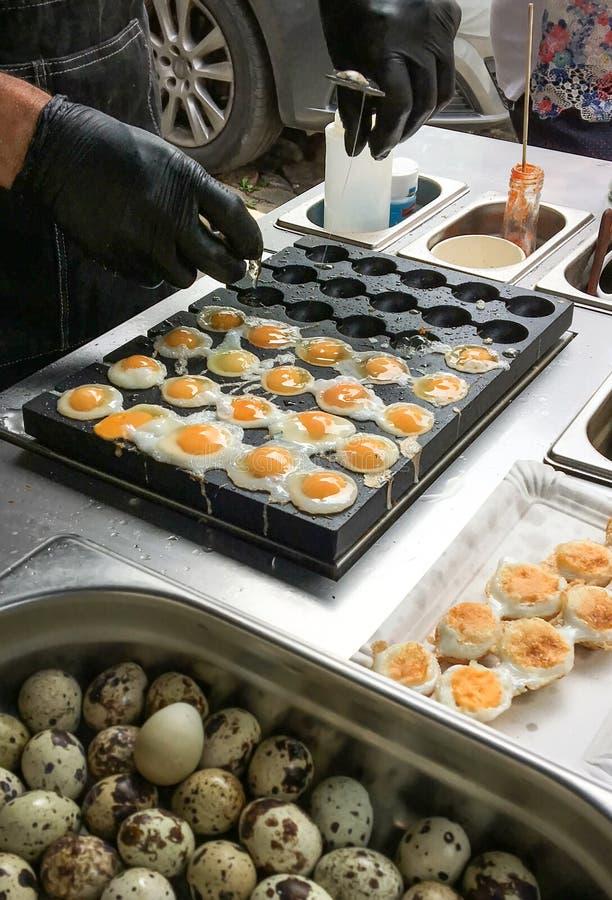 Freír los huevos de codornices en la estufa en el bazar fotos de archivo