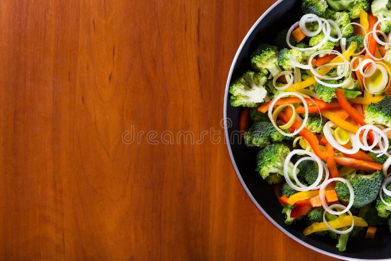 Freír verduras en cacerola con el fondo de madera foto de archivo libre de regalías