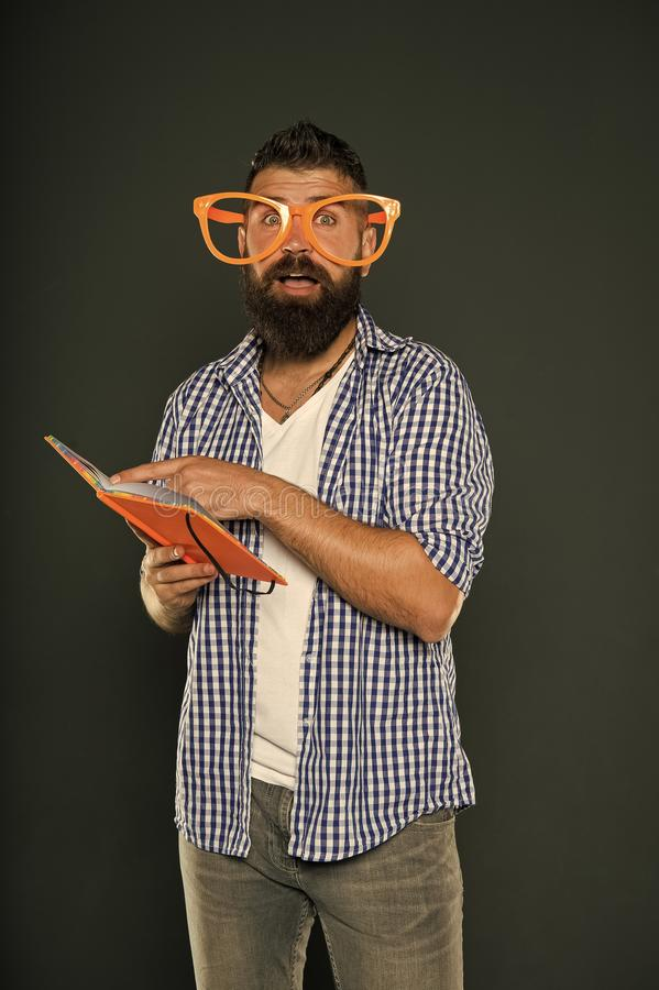 Freak and geek. Bearded man in party glasses reading book. Study nerd holding lesson book. University male student with. Lecture notes. Book nerd wearing fancy stock image