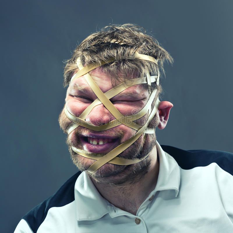 Freak man with rubber on his face. Isolated on gray royalty free stock images