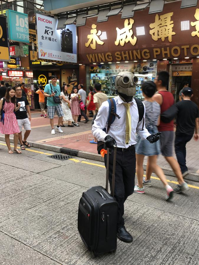 Freak in steampunk helmet in Hong Kong street. HONG KONG - SEPTEMBER 17, 2017: An unidentified man wearing a steampunk helmet is going to perform in a Hong Kong stock image