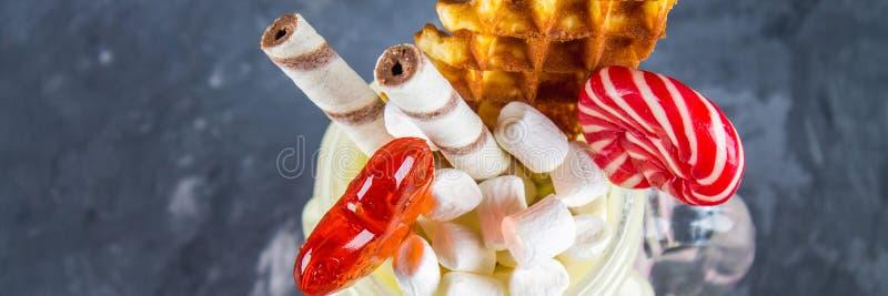 Freakshake από το ρόδινο καταφερτζή, κρέμα Monstershake με τα lollipops, τις βάφλες και marshmallow Ακραίο milkshake σε ένα βάζο  στοκ φωτογραφία