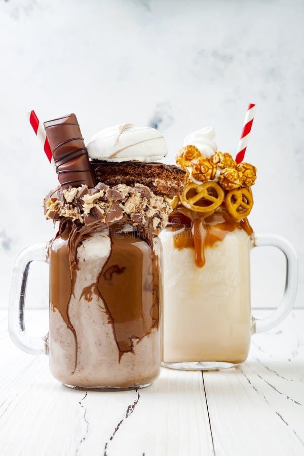Freakshake pazzo del cioccolato e del caramello, frappé con le cialde del brezel, popcorn, caramella gommosa e molle, gelato e pa immagine stock
