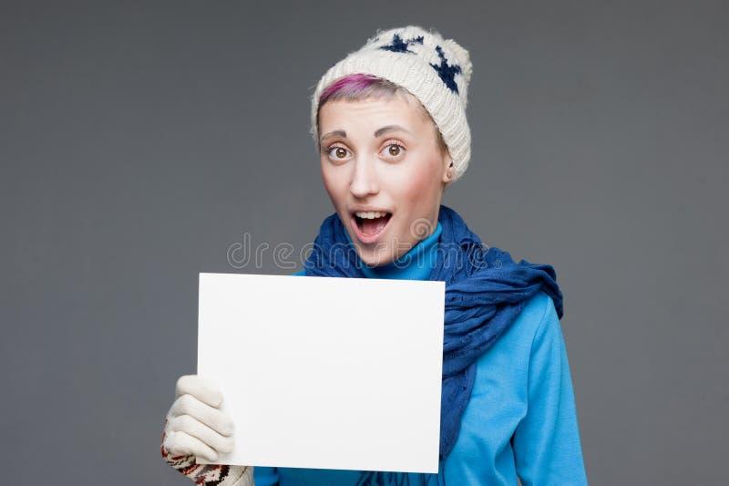 Freaky девушка в знаке удерживания одежды зимы стоковые изображения