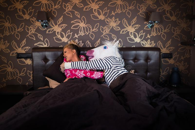 Unusual couple has relationship problems. Freaky men in unicorn mask molest to scared girlfriend in pajama in bed. Unusual couple has relationship problems in royalty free stock photography