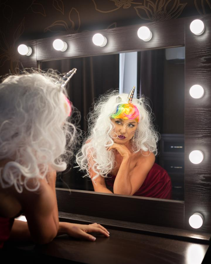 Freaky young woman in unusual wig looks at himself royalty free stock images