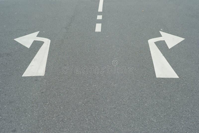 Frecce al a destra e a sinistra su una via - un concetto per le decisioni fotografia stock