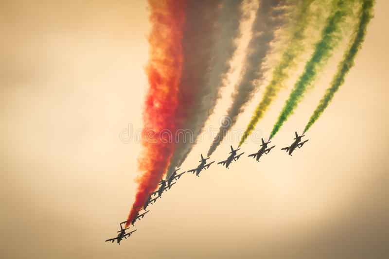 Frecce Tricolori alona : italian aerobatic Team performing a low pass with italian flag colors smokes in sunset. Frecce Tricolori: italian aerobatic Team stock images