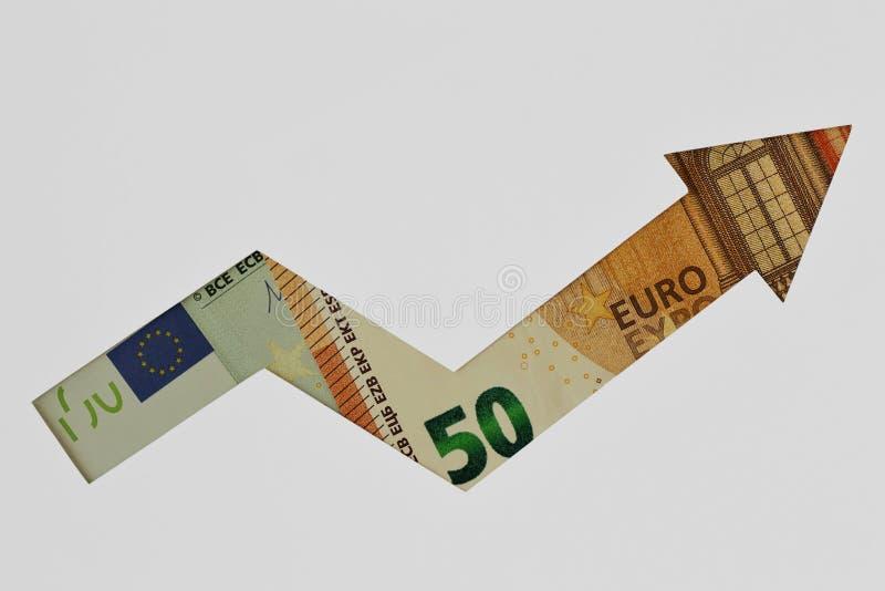 Freccia ascendente fatta di euro banconote su fondo bianco - concetto della tendenza al rialzo di euro valuta fotografia stock libera da diritti