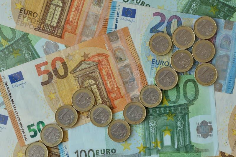 Freccia ascendente fatta di euro monete sull'euro fondo delle banconote - concetto della tendenza al rialzo di euro valuta immagine stock libera da diritti
