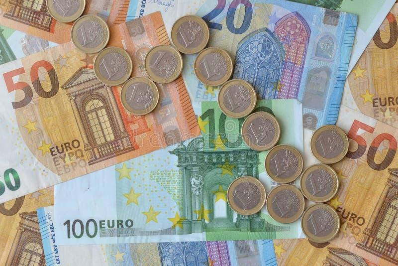 Freccia discendente fatta di euro monete sull'euro fondo delle banconote - concetto della tendenza verso il basso di euro valuta fotografia stock libera da diritti