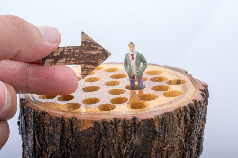Freccia e piccoli posti della figurina dell'uomo sul ceppo di legno immagini stock