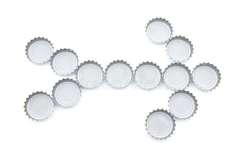 Freccia fatta dei cappucci utilizzati della birra fotografia stock libera da diritti