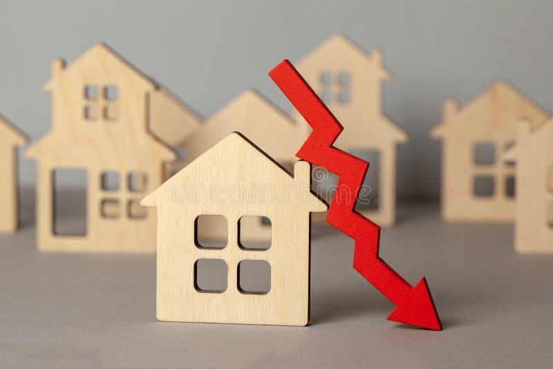 Freccia giù e molte case Mercato di caduta di prezzi del bene immobile Comprando e vendendo casa fotografia stock libera da diritti
