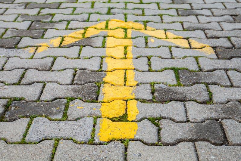 Freccia gialla dipinta su pavimentazione grigia, segnale di direzione della strada fotografie stock