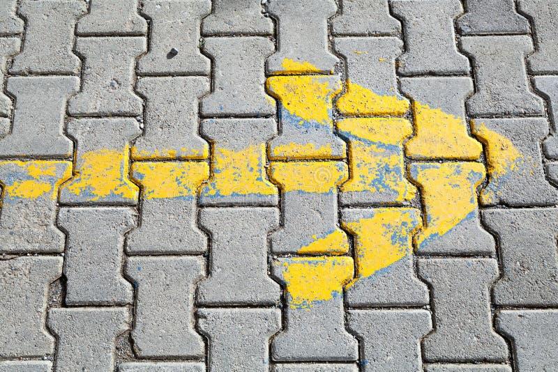Freccia gialla dipinta sulla pavimentazione grigia del ciottolo fotografia stock libera da diritti