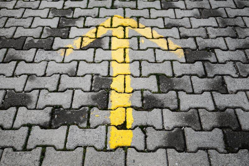 Freccia gialla dipinta sulla pavimentazione grigio scuro del ciottolo immagine stock libera da diritti