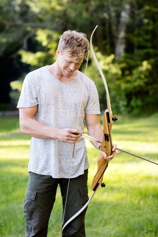 Freccia maschio sicura di Archer Holding Bow And in foresta immagine stock
