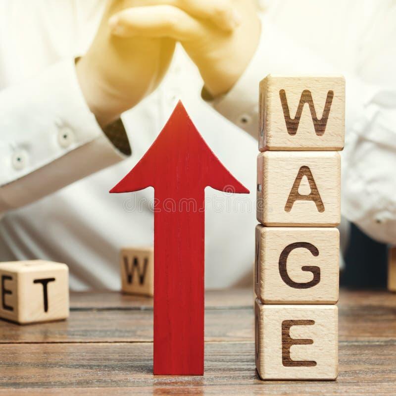 Freccia rossa su vicino ai blocchi di legno con lo stipendio di parola e un uomo d'affari Concetto di aumento di salario Tasso di fotografia stock