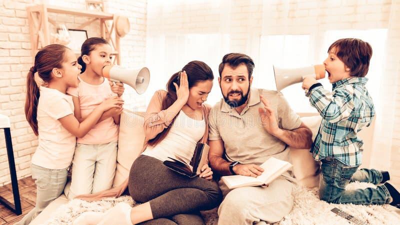 Freche Kinder, die Eltern-Lesebücher stören lizenzfreie stockbilder