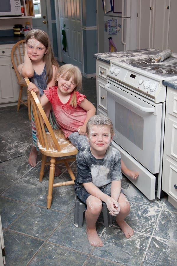 Freche Kinder, die Verwirrung in der Küche machen lizenzfreie stockfotografie