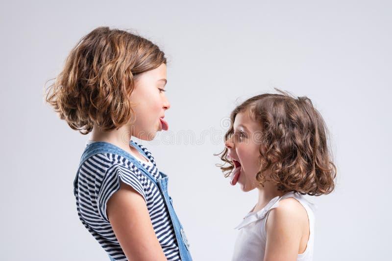 Freche kleine Schwestern, die heraus ihre Zungen haften lizenzfreies stockbild