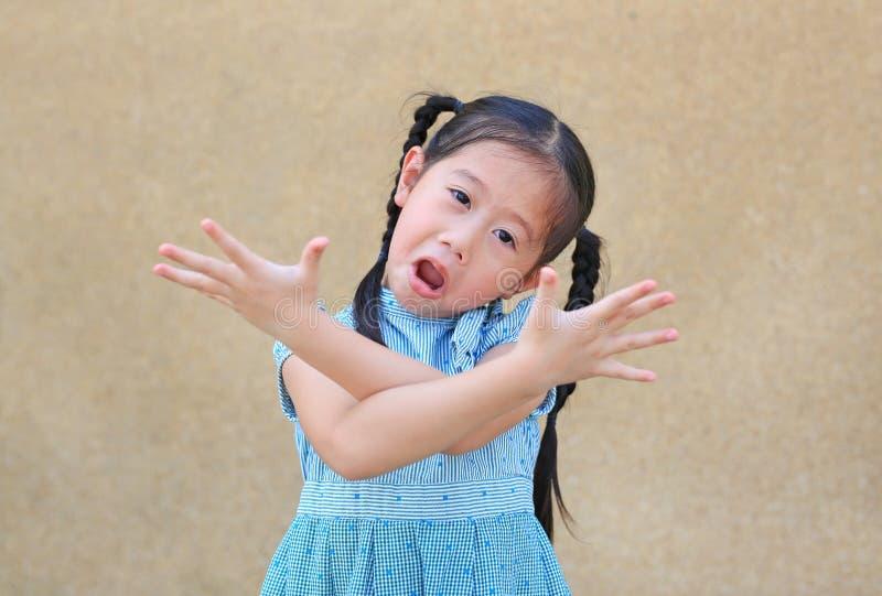 Freches kleines asiatisches Kindermädchen mit lustigem Gesicht und Ausdruck kreuzen irgendjemandes Arm lizenzfreie stockbilder
